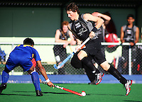 NZ's Simon Childs goes round Muhammad Razie Abdul Rahim during the international hockey match between the New Zealand Black Sticks and Malaysia at Fitzherbert Park, Palmerston North, New Zealand on Sunday, 9 August 2009. Photo: Dave Lintott / lintottphoto.co.nz