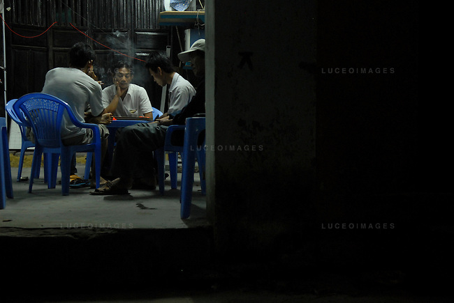 Vietnamese men play a board game in Hoi An, Vietnam.