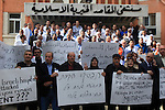 Palestinian doctors and medical employees take part in a protest outside the al-Makassed Hospital against the storming of the hospital by Israeli police, in east Jerusalem on October 29, 2015. Palestinian Minister of health Jawad Awwad denounced storming al-Makassed Hospital for the third time in a month, attacking staff and firing teargas canisters within the premises. He called on the international community to immediately interfere to put an end to Israeli crimes against the Palestinians. Photo by Mahfouz Abu Turk