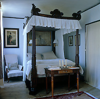 A simply dressed 19th century four-poster bed is surrounded by Scottish portraits