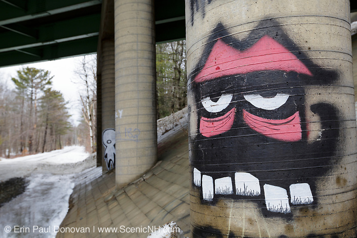 Graffiti on bridge overpass along railroad tracks in Plymouth, New Hampshire USA. This section of railroad is operated by The Hobo and Winnipesaukee Scenic Railroads.