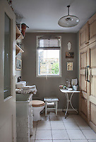 The bathroom has a white tiled floor and built-in floor-to-ceiling cupboards