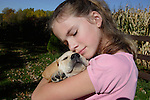 12 year old girl hugs ( a little too hard) a yellow Labrador retriever puppy (AKC).  Fall.  Birchwood, WI
