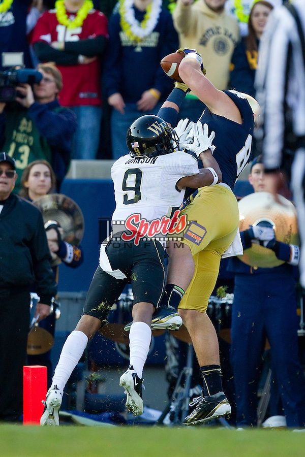 Tyler Eifert (80) of the Notre Dame Fighting Irish catches a touchdown pass in front of Kevin Johnson (9) at Notre Dame Stadium on November 17, 2012 in South Bend, Indiana.  The Fighting Irish defeated the Demon Deacons 38-0.  (Brian Westerholt/Sports On Film)