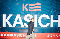 A campaign staffer walks past the campaign bus outside while Ohio governor and Republican presidential candidate John Kasich speaks at a town hall campaign event at Raymond VFW Post 4479 in Raymond, New Hampshire, on Wed., Feb. 3, 2016.