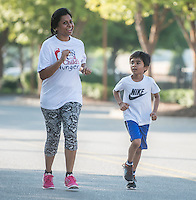 NWA Democrat-Gazette/ANTHONY REYES &bull; @NWATONYR<br /> Smita Sharda, and her son Krish Sharda, 7, run in the one mile fun run Monday, Sept. 7, 2015 at the 12th Annual Run for a Child's Hunger race at the Promenade in Rogers. The race has teamed up with Care Community Center to help fight hunger in the region. The event featured multiple activities including a 10K race, 5K race, fun run, inflatable playground for children and a free breakfast.