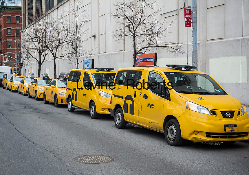 A line of idling cabs as drivers take a break in New York on Wednesday, April 5, 2017. An NYC taxi medallion recently sold for $241,000, down from a high of $1.3 million just four years ago. Because of the rise in Uber, Lyft and other ride-sharing apps taxi medallions have plummeted with loan delinquencies on the rise.  (© Richard B. Levine)