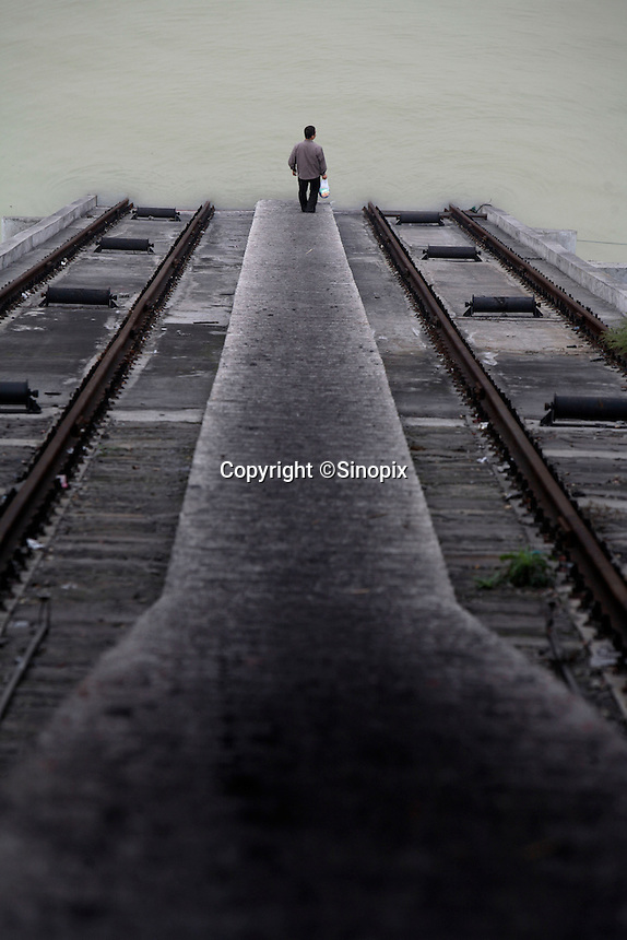 A man walks down the steps of a coal loading dock along the Yangtze River in Wanzhou District, Chongqing, China..19 Oct 2007