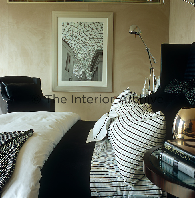 In a London bedroom black and white bedding is juxtaposed against faux-suede grey walls on which hangs a photograph of the Great Court of the British Museum