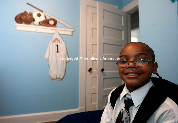 WATERBURY, CT-17 MAY 2010-051710JS14-Neftali McNeil, 8, of Waterbury, sits in his newly painted bedroom at his home on Chestnut Avenue in Waterbury on Monday. His room was painted as part of a program through the Salvation Army that works with needy families to get them houseing and then paints the childrens room.<br /> Jim Shannon Republican-American