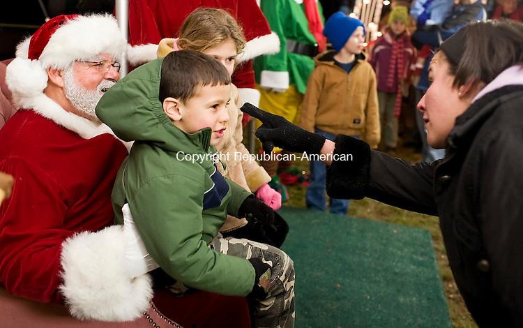"THOMASTON, CT--24 November 07--112407TJ03 - ""Tell Santa what you want,""Trudy Torre, from Waterbury, tells her son, Evan, 4, who shares Santa's lap with his sister, Alexa, at the 13th annual Light Up Thomaston celebration on Saturday, November 24, 2007. T.J. Kirkpatrick/Republican-American"