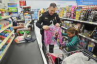 NWA Media/Michael Woods --12/06/2014-- w @NWAMICHAELW...Detective Bryan Lindabury with the Fayetteville Police Department helps Hali Smart, age 6 from Fayetteville, check out after shopping for clothes and toys Saturday morning during the shop with a cop event at Walmart on MLK Blvd in Fayetteville.  Several local law enforcement agencies participating in the annual event to help local children, the Fayetteville police department help out about 100 local children during the event.