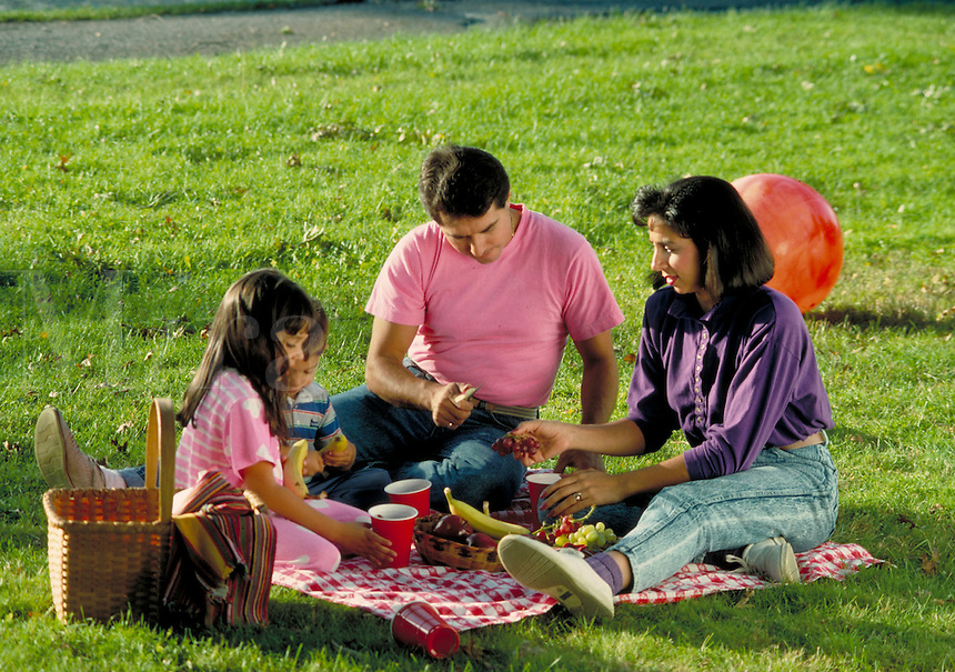 Four year-old boy and seven year-old girl, son and daughter, enjoy picnic food on the lawn in a park with young mother and father, a family outing. Family.