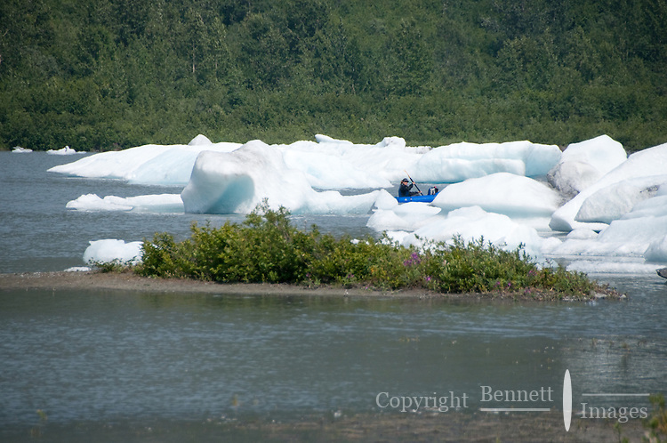 A pack rafter ventures among the icebergs as she starts across the lake.