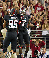 STANFORD, CA - October 5, 2013:  Stanford Cardinal players Luke Kaumatule (99) and Ty Montgomery (7) celebrate Montgomery's touchdown during the Stanford Cardinal vs the Washington Huskies at Stanford Stadium in Stanford, CA. Final score Stanford Cardinal 31, Washington Huskies  28.