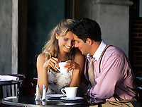 A smiling, affectionate young couple enjoy coffee in a cafe together.