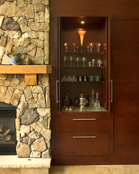 Detail of a wall of cherry cabinets. The cabinets conceal a bar and audio/video components.