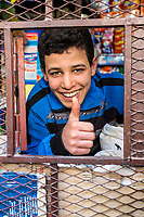 Fes, Morocco.  Young Man at Window of a Small Neighborhood Sundries Store.