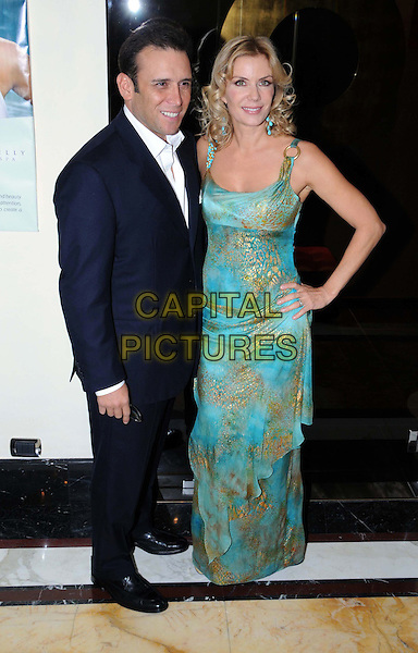 """KATHERINE KELLY LANG & GUEST.American Actress Katherine Kelly Lang at the Rome Opening of her Beauty Center """"Kelly Spa"""", Rome, Italy..October 1st, 2008.full length blue turquoise gold pattern long maxi dress hand on hip black suit .CAP/ADM/Liverani/MB.©Massimo Bruni/Liverani/AdMedia/Capital Pictures"""