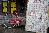 Red bicycle parked behind a long list of menu prices by a restaurant in Datong, Shanxi, China.