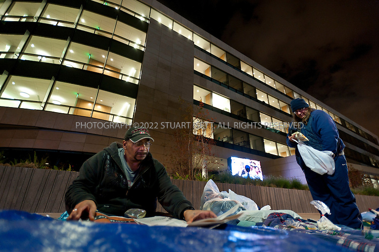 10/12/2011--Seattle, WA, USA..Homeless in Seattle, organized by SHARE (Seattle Housing and Resource Effort), camp outside the Bill and Melinda Gates Foundation in Seattle, WASH. SHARE runs 15 shelters in Seattle and says cuts in government funding have forced it to close the shelters and put 300 people onto the street. The 'sleepout' at the Gates Foundation started on Monday, Oct. 10th, with about 50 homeless camping out with blankets and tarps; SHARE organizers have asked the Gates Foundation for funds to support its local efforts to fight homelessness and reopen the closed shelters...HERE: Alan Taylor, 51 (left) homeless for 1 1/2 years reads a newspaper while Colin Macleod, 38 (right), homeless for 3 years sets up his bed...©2011 Stuart Isett. All rights reserved.