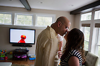 Fred Bermont kisses wife Jen Bermont before she leaves for work while holding son Dylan Bermont (age 9 months) in their home in Lexington, Massachusetts, USA, before he goes to work on June 9, 2014. Bermont is the father of two children and shares parenting duties with his wife, Jen Bermont. Fred usually takes care of the morning routine, including feeding, dressing, and dropping the kids off at day-care, and Jen picks them up and watches over them in the afternoon. Fred is a Senior Clinical Standards Specialist at Shire, a pharmaceutical company with headquarters in Lexington.