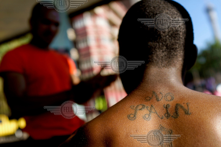The words 'No Pain' tattooed on the back of Sandile Khumalo, a professional boxer who trains at the Hillbrow Boxing Club.