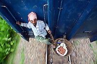 A hawker selling onions sits precariously with his basket of wares on a coupling between two train carriages. In Bangladesh many people ride on the roofs of trains as frequently that is the only space available. For others, the fares are too high and can be avoided or reduced by travelling on the roof. However, the riding on roofs and other parts of train exteriors leads to regular accidents, many of them fatal.