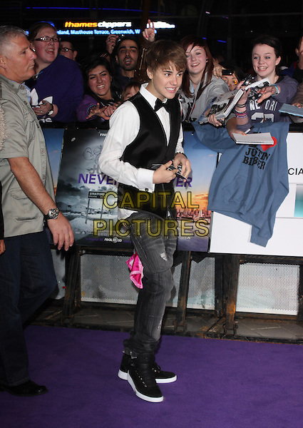 JUSTIN BIEBER.The UK Premiere of Justin Bieber: Never Say Never, Cineworld, 02 Arena, London, England..February 16th, 2011.full length black velvet waistcoat bow tie white shirt jeans denim side smiling funny trainers hi-tops ripped denim .CAP/ROS.©Steve Ross/Capital Pictures.