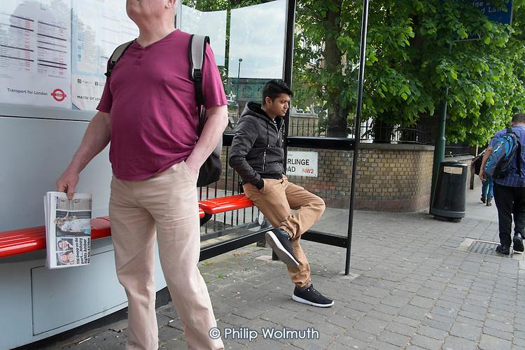 Young man waiting at a bus-stop, Kilburn, London.