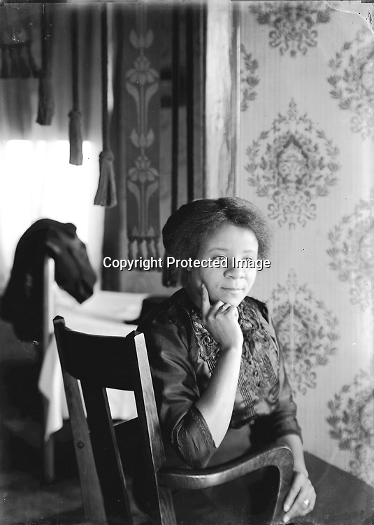 CONTEMPLATIVE FRANCES HILL. Photographing in homes posed special challenges in the days of bulky view cameras and flash powder. John Johnson apparently took few interior photographs but accomplished some effective images. If the rings on both hands are an indication of marriage, this may be one of the very latest Johnson images. Frances Hill (1904-1932) married Bert Taylor around 1929 or 1930 and moved to New York City, where she died in 1932. This interior is probably in the home of John C. and Mabel Galbreath, with whom Hill lived for most of the 1920s.<br /> <br /> The 1920 census shows Aaron Douglas, 21 year old University student, was a roomer in the household of Ben. F. &amp; Lottie Corneal. Ben was head of the waiters club of Lincoln; a second roomer was a barber. They resided at 524 N. 9th--a couple of blocks south of Mamie Griffin's house at 915 U. The Corneals next door neighbors were John and Mable Galbreath at 524 N. 9th. John was sometimes a waiter; in 1920 he was listed as operating a restaurant. John and Mable also had a roomer, as well as a stepdaughter--15 year old Frances Hill. <br /> <br /> Photographs taken on black and white glass negatives by African American photographer(s) John Johnson and Earl McWilliams from 1910 to 1925 in Lincoln, Nebraska. Douglas Keister has 280 5x7 glass negatives taken by these photographers. Larger scans available on request.