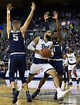 Nevada forward Cody Martin drives past Utah State guards Sam Merrill (5) and Tauriawn Knight (1) in the first half of an NCAA college basketball game in Reno, Nev., Wednesday, Jan. 2, 2019. (AP Photo/Tom R. Smedes)