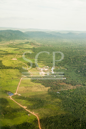 Pará State, Brazil. Cattle ranch country near Ourilândia; boundary between cleared area and forest with road running through.