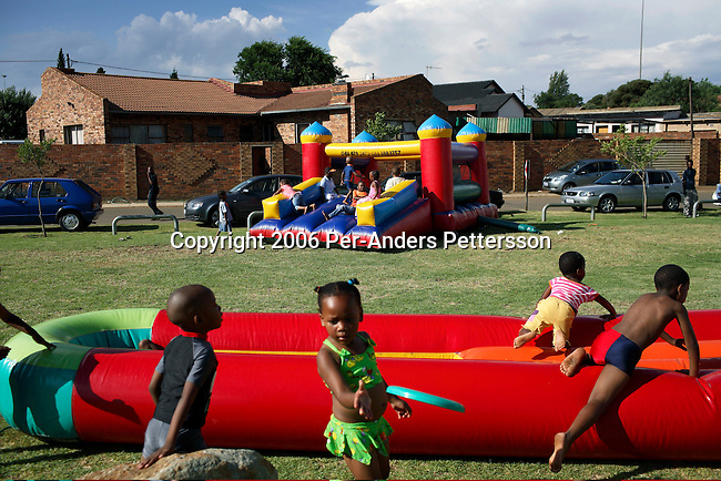 SOWETO, SOUTH AFRICA DECEMBER 10: Children play next to a jumping castle during a birthday celebration on December 10, 2006 in Thokoza park in Soweto, Johannesburg, South Africa. Most birthdays for children have these jumping castles where the children play, and it usually takes up the whole garden. Soweto is South Africa?s largest township and it was founded about one hundred years to make housing available for black people south west of downtown Johannesburg. The estimated population is between 2-3 million. Many key events during the Apartheid struggle unfolded here, and the most known is the student uprisings in June 1976, where thousands of students took to the streets to protest after being forced to study the Afrikaans language at school. Soweto today is a mix of old housing and newly constructed townhouses. A new hungry black middle-class is growing steadily. Many residents work in Johannesburg, but the last years many shopping malls have been built, and people are starting to spend their money in Soweto. .(Photo by Per-Anders Pettersson/Getty Images)..