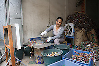 A migrant worker melts metal components off a circuit board from a chuck of electronic trash in Guiyu in southern China's Guangdong province.  Each year, between 20 and 50 million tons of electronic waste is generated globally. Most of it winds up in the developing world. Some of the most popular destinations for dumping computer hardware include China, India, and Nigeria. It can be 10 times cheaper to ship waste to China than to dispose of it properly at home. With the market for e-waste expected to top $11 billion by 2009, it's lucrative to dump on the developing world.