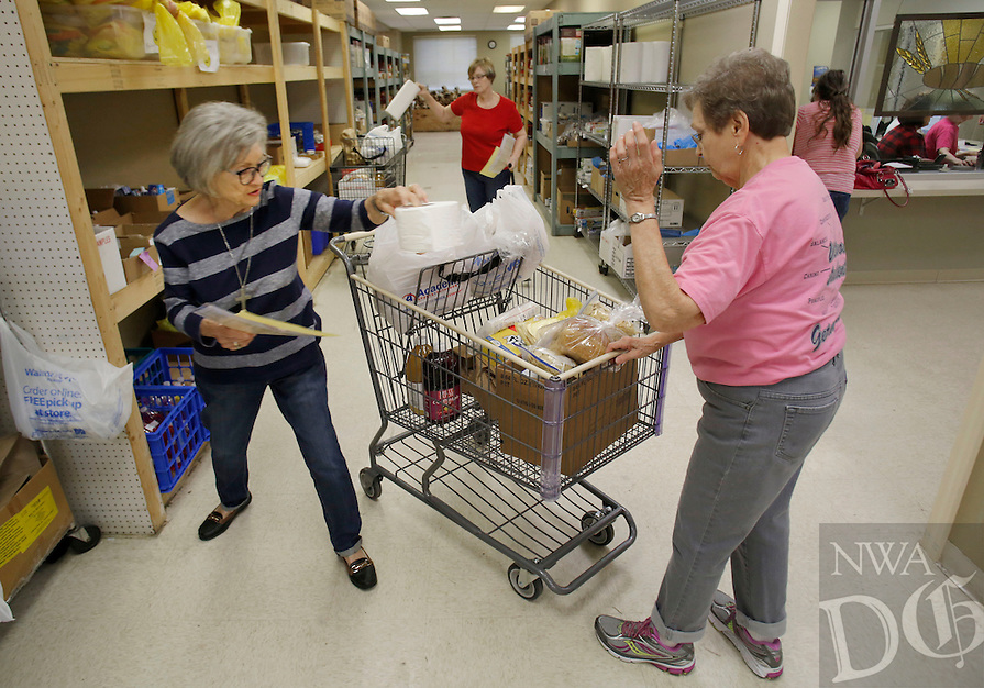 NWA Democrat-Gazette/DAVID GOTTSCHALK  Anita Ellison (from right), a new volunteer, fills food request with Karen Smoyer, an eight month volunteer, and Karen Chambers, a nine year volunteer, Wednesday, November 2, 2016, at the Bread of Life food pantry at First United Methodist Church in Springdale.