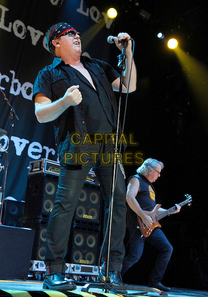 "Mike Reno and Ken ""Spider"" Sinnaeve.Legendary hit rockers Loverboy opened for Journey in Atlanta on their 2012 tour at Aaron's lakewood Amphitheater, Atlanta, GA., USA..October 6th, 2012 .on stage in concert live gig performance performing music full length black shirt sunglasses shades side profile guitar singing jeans denim.CAP/ADM/DH.©Dan Harr/AdMedia/Capital Pictures."