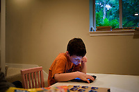 "Jack Ursitti, age 7, uses an iPad to play a spelling game in his home in Dover, Mass., on Monday, July 25, 2011. The game asks Jack to spell three-letter words that accompany pictures. Jack has been diagnosed with autism.  After school at his home, Jack works with his teacher and a therapist to do educational and independent leisure activities. ..Jack received an iPad for Christmas, according to his mother Judith Ursitti. ""I wanted mine back,"" said Judith. She had gotten an iPad for her birthday in 2010, and Jack used it constantly. ""There's something intuitive about it,"" said Judith.  In the beginning it was just a distraction, ""but now we're moving to use it for an educational purpose,"" she said...Jack Ursitti wears a small GPS ankle bracelet at all times in case he runs off from his family or caretakers. The device will be activated if he goes missing, allowing police and other searchers to find him."
