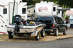 Bass boat and SUV parked in camp with RVs in background