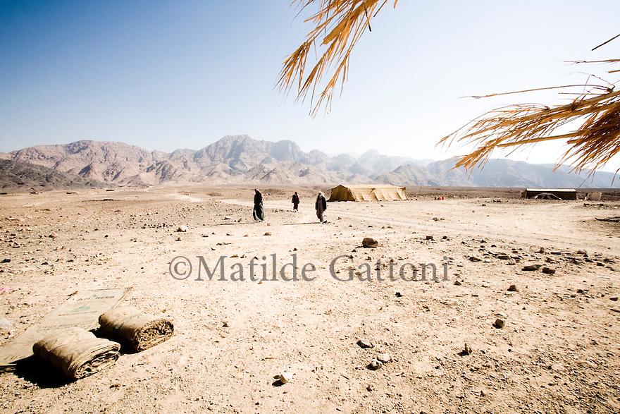 Jordan, Beduin men walking in the desert close to their campement in Wadi Faynan