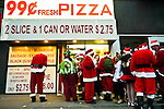 NEW YORK, NY - DECEMBER 15: Revelers dressed as Santa Claus wait in line for 99 cent Pizza during the annual SantaCon event December 15, 2012 in New York City. (Photo by Donald Bowers)