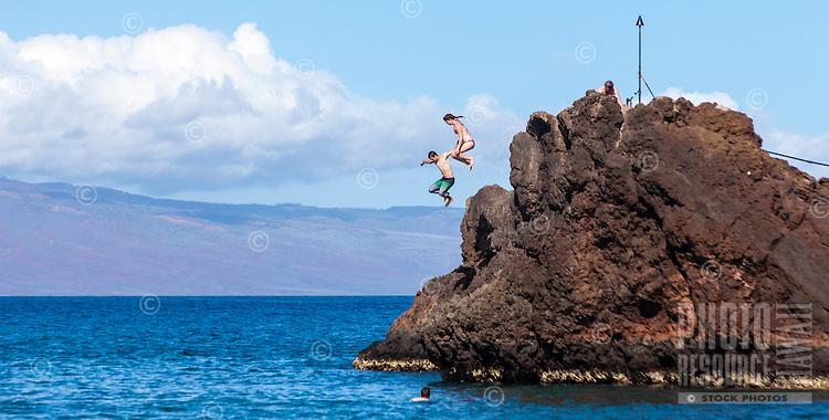 Two adventurers jump off Black Rock at Ka'anapali Beach on Maui.