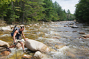 Backcountry hiker crossing the East Branch of the Pemigewasset River in the Pemigewasset Wilderness of Lincoln, New Hampshire.