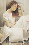 Girl with red hair and long white flowery summer dress sitting on the floor between white cushions with thoughtful expression