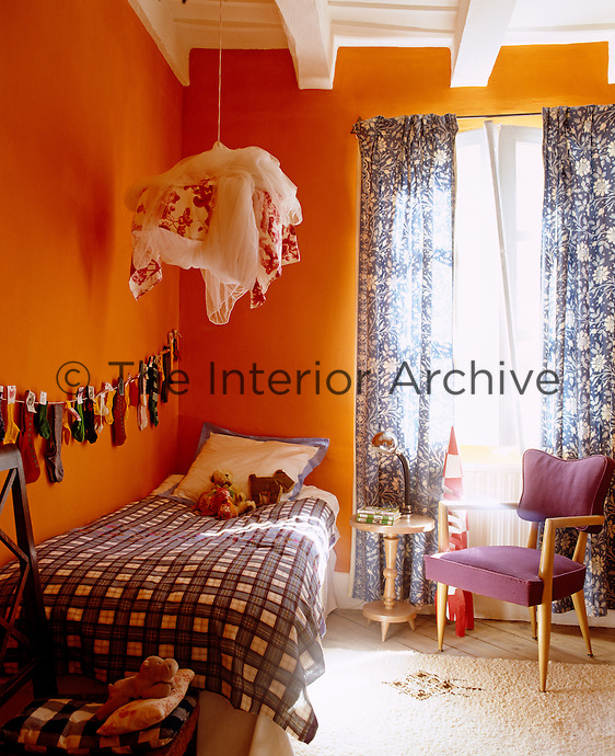 Pairs of socks hang in a line along one wall of this cheerful orange-painted child's bedroom