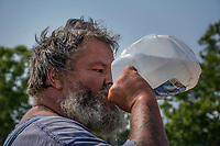Farmer drinks from a gallon jug of water while taking a break from spraying herbicide on a field at the Braun Farm in Westerville, Ohio.