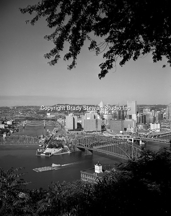 Pittsburgh PA:  View of Pittsburgh with Tugboat taking barges down the Ohio River - 1959