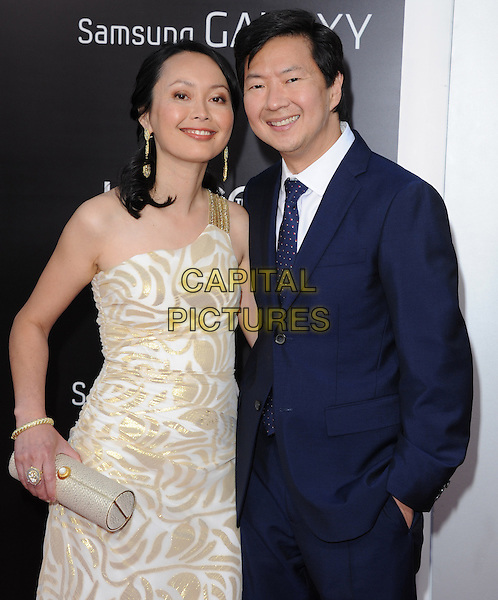 """Tran Ho & Ken Jeong.""""The Hangover Part III"""" Los Angeles Premiere held at the Westwood Village Theater, Los Angeles, California, USA..May 20th, 2013.half length blue tie suit shirt white gold white pattern one shoulder dress married husband wife clutch bag.CAP/DVS.©DVS/Capital Pictures"""