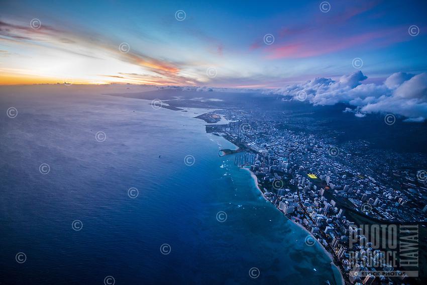A high-elevation view at dusk of Waikiki, downtown Honolulu and beyond, O'ahu.