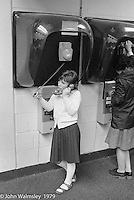 Student making a call from the public payphone at the Education Centre, Wester Hailes, Scotland, 1979.  John Walmsley was Photographer in Residence at the Education Centre for three weeks in 1979.  The Education Centre was, at the time, Scotland's largest purpose built community High School open all day every day for all ages from primary to adults.  The town of Wester Hailes, a few miles to the south west of Edinburgh, was built in the early 1970s mostly of blocks of flats and high rises.